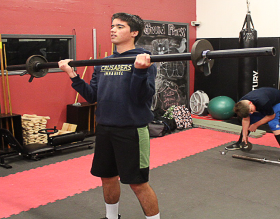 Eighth Grader, Hayden Parker, works out his biceps with the axel bar