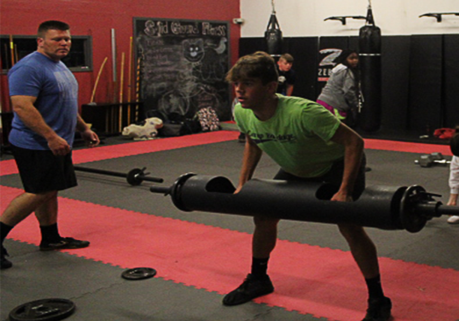 Junior+Spencer+Jennings+performs+a+bent+over+row+while+Coach+Clark+looks+on.+