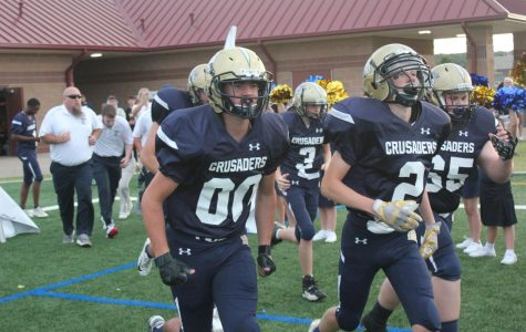 The Crusaders football team storms the field on Sept. 13 for a 16-10 win against Bowlegs.